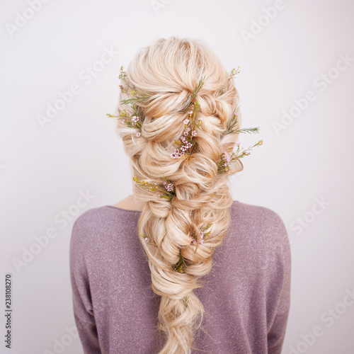 Obraz Back view of an elegant trendy hairstyle, interlacing curls and decorating with flower petals - fototapety do salonu