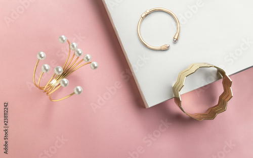 Fotografía  Golden bracelet with pearls and golden zigzag shape cuff on pink and white paper