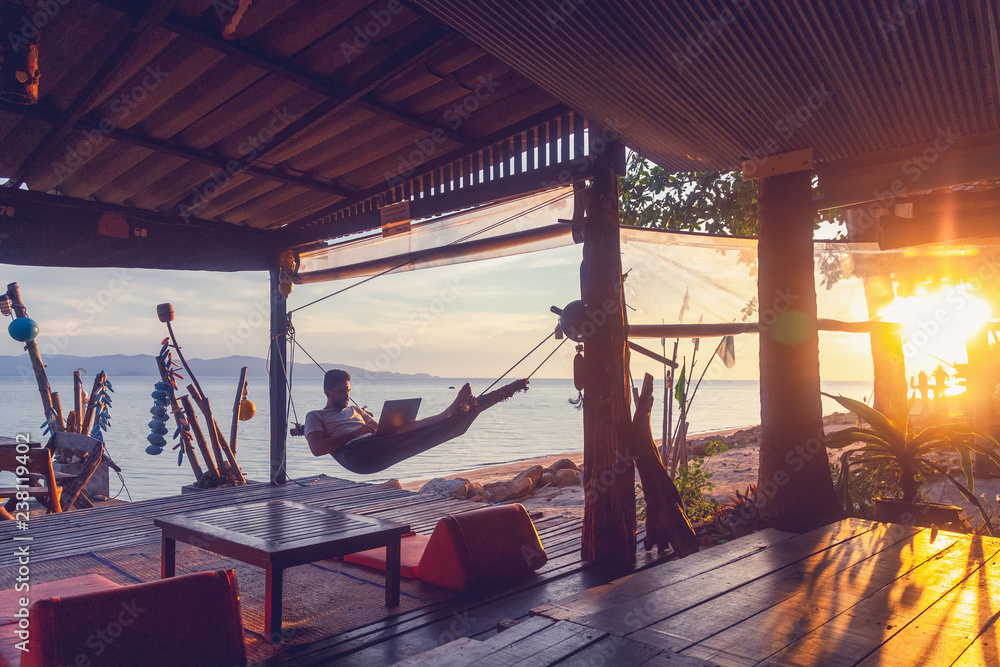 Fototapety, obrazy: Young attractive guy a man with a beard in a hammock with a laptop on the background of the sea and sunset, distant work, freelancer, blogger, vacation and travel