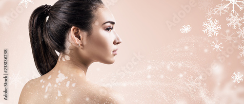 In de dag Spa Young woman over beige background with snowflakes.