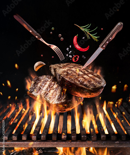 Raw beef steaks with vegetables and spices fly over the blazing grill barbecue fire.