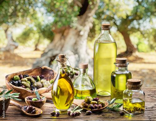 Oliwa z oliwek i jagody są na drewnianym stole pod drzewem oliwnym.