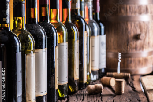 Wine bottles in row and oak wine keg. Fototapeta