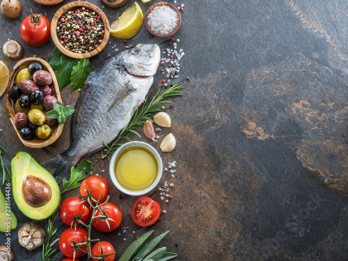 Fotografie, Obraz  Raw dorado fish with spices and vegetables on the graphite board.
