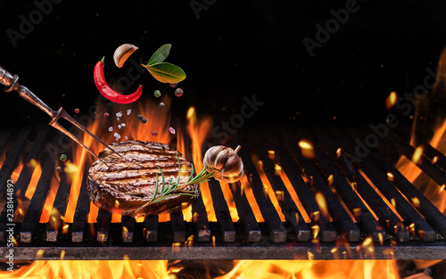 Beefsteak with spices fly over the flaming grill barbecue fire.