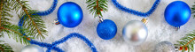 New Year Banner With Blue And Silver Christmas Balls In Snow, Spruce Green Branches On White Background. Xmas Decoration. Merry Christmas.
