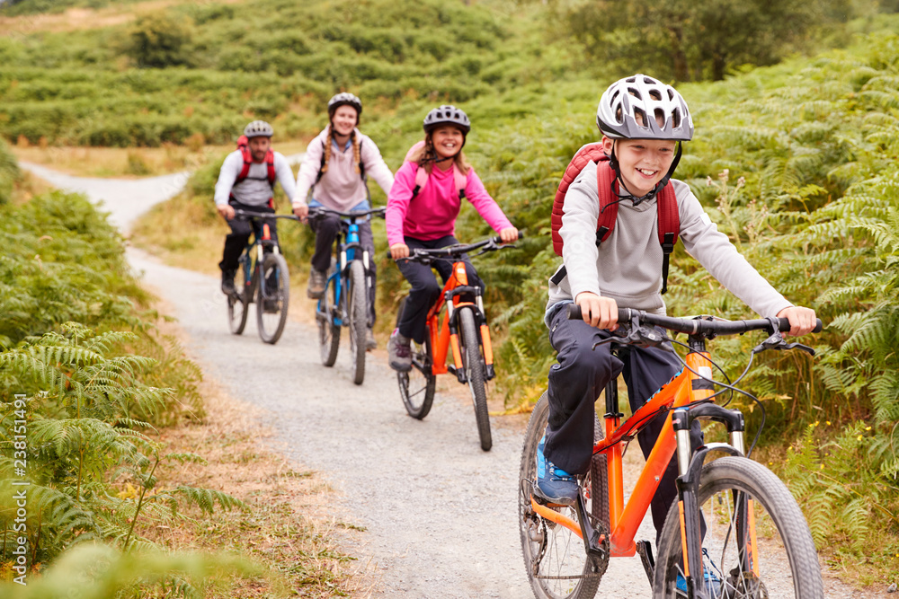 Fototapeta Pre-teen boy riding mountain bike with his sister and parents during a family camping trip, close up