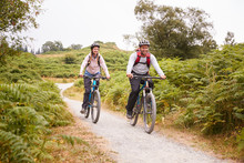 Young Adult Couple Riding Mountain Bikes In The Countryside, Full Length