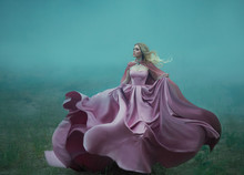 Blonde In The Fog In A Light Long Expensive Royal Dress Fluttering On The Fly, Takes The Form Of A Magic Flower, A Delightful Photo In Motion. An Excerpt From The Life Of A Fantastic Character Girl