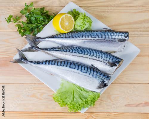 Raw carcasses of Atlantic mackerel with lemon and greens