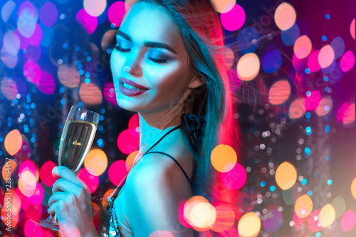 Sexy model girl with glass of champagne at disco party, drinking champagne over holiday glowing blue background. Beauty woman with perfect fashion makeup