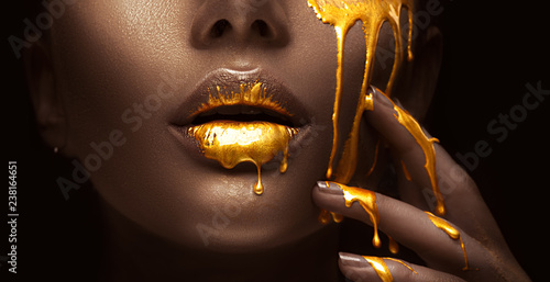 Autocollant pour porte Fashion Lips Golden paint smudges drips from the face lips and hand, golden liquid drops on beautiful model girl's mouth, creative abstract makeup. Beauty woman face