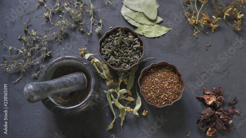 Photo  Herbal medicine preparation with fresh herbs and flowers, aromatherapy essential oil, mortar with pestle and scissors on hemp paper background