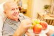 canvas print picture - Pflegehilfe serviert altem Mann Obst
