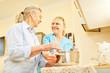 Senior Frau und Pflegehilfe kochen zusammen