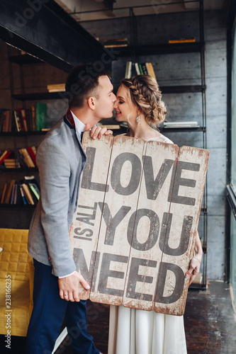 Photo  Portrait of lovely newlywed couple holding wooden signboard with message all you need is love