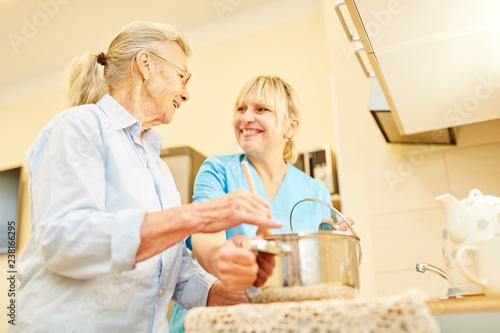 Fototapeta Senior Frau und Pflegehilfe kochen zusammen obraz