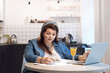 Picture of serious concentrated overweight female working through finances, sitting in kitchen with papers and open laptop on round table. People, modern technology, lifestyle and occupation