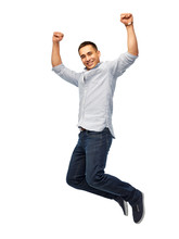 Triumph, Power And People Concept - Happy Young Man Jumping Over White Background