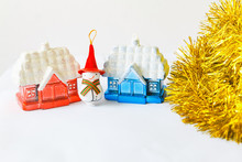 New Year's Toys. A Snowman In A Big Red Cap Stands Between The Red And Blue Houses. Gold Tinsel Is Nearby