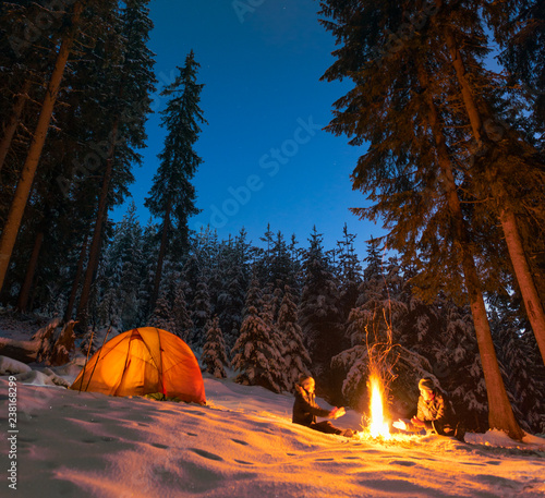 Fotografia couple camping with campfire and tent outdoors in winter