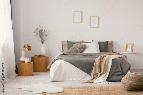 Fotografie, Obraz  Flowers on wooden stool and pouf in white bedroom interior with posters above bed