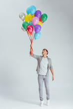 Handsome Man Standing On Tiptoe And Holding Bundle Of Colorful Balloons On Grey Background