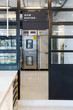 Modern pastry kitchen entrance with Now Baking board decorated in black and white steel with baking machine and oven inside.