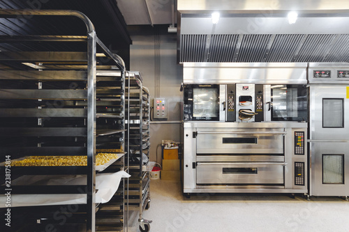 Foto op Plexiglas Bakkerij Modern pastry kitchen decorated in black, white and steel with baking machine, oven, conveyor, production line, mixer and cooling plant.
