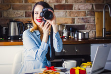 Beautiful Young Photographer Have A Coffee Break While Sitting Working With Camera And Laptop. Concept Of Work With Startup Business In Holiday Time
