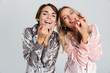 Two pretty girls wearing pajamas isolated over gray