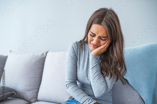 Fotografia  Beautiful Young Woman Suffering From Terrible Strong Teeth Pain, Touching Cheek With Hand