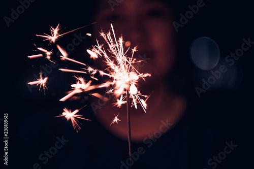 Hand holding burning Sparkler blast on a black background at night,holiday celebration event party,dark vintage tone Billede på lærred