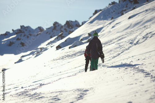 Fotografía  Freeriders climb the snow-covered mountain slope.