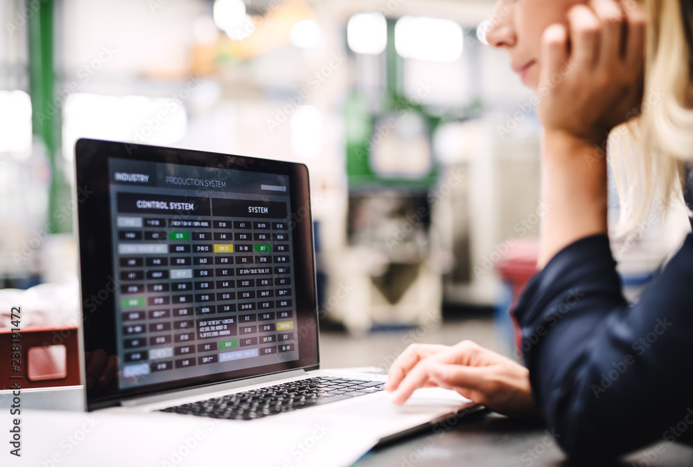 Fototapety, obrazy: An industrial woman engineer in a factory using laptop.