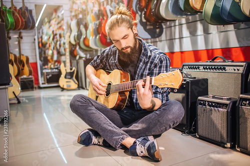 Photo Stands Music store Calm and concentrated young man sit on floor with legs crossed. He playes on acoustic guitar. Many electric guitars and sound speakers are in room. Guy sits alone.