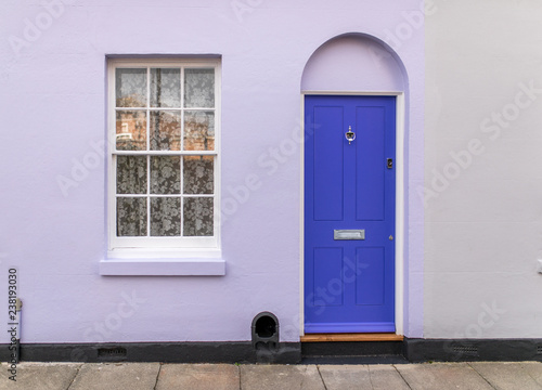 Fotografie, Obraz  Typical english house facade with lavender color door and white window viewed from outdoors