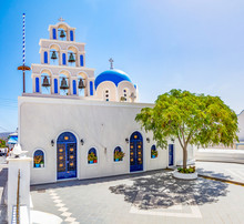 Holy Trinity Church With Bell Tower And Blue Domes In Akrotiri, Santorini, Greece