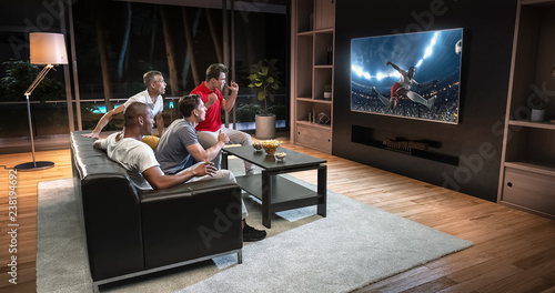Fotografía  Group of students are watching a soccer moment on the TV and celebrating a goal, sitting on the couch in the living room