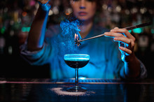 Bartender Girl Adding To A Brown Cocktail A Flamed Badian With Tweezers In The Blue Light
