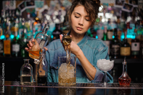 Bartender girl pouring to the measuring glass cup with ice cubes an alcoholic drink from jigger