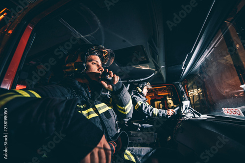 Photo Two Fireman Man posing inside the truck