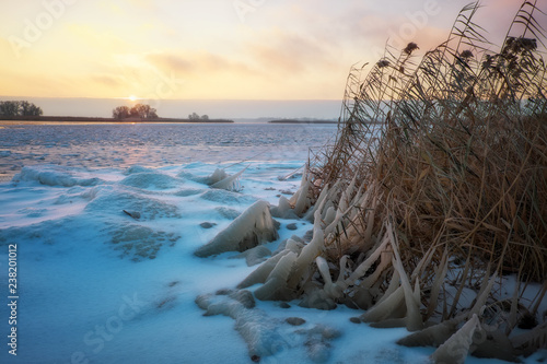 Foto auf Gartenposter Blau Jeans Winter landscape with frozen lake and sunset fiery sky. Composition of nature.