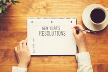 New Years Resolution With A Person Holding A Pen On A Wooden Desk