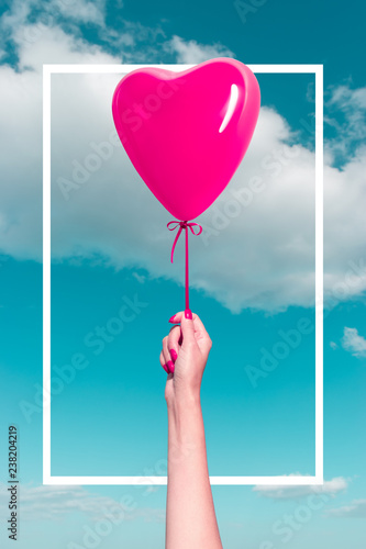 Photographie  Womans hand with heart shaped balloon on background of sky