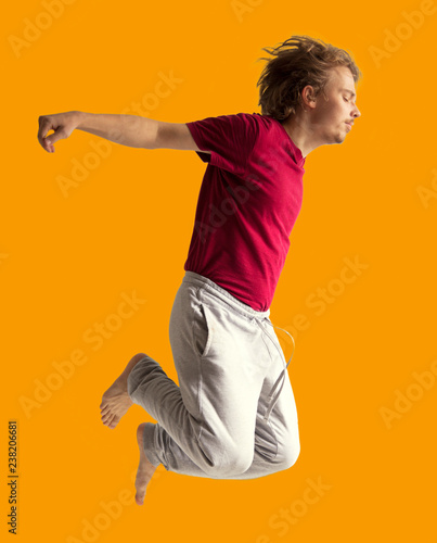 Aluminium Prints Superheroes teenager boy jumping dance movement on a colored yellow background