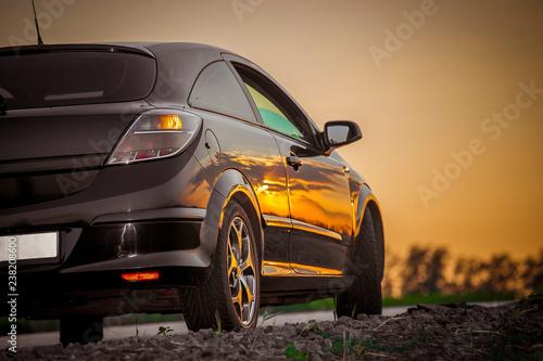 Fototapeta beautiful black modern car stands on asphalt road in summer illuminated by the rays of the sunset obraz na płótnie