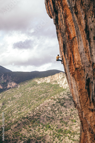 Spoed Fotobehang Alpinisme man climbs an overhanging edge of the cliff in Greece, near the valley and trees
