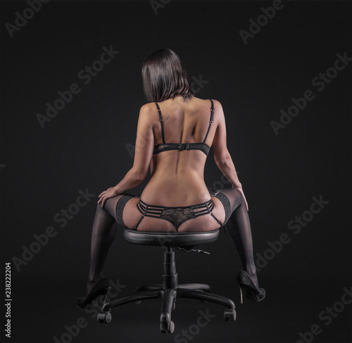 Fotografía  Sexy young brunette woman in black sensual lingerie posing on black background wall in studio