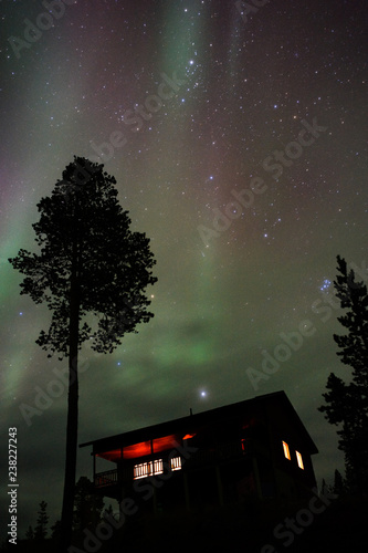 Night sky with Aurora Borealis, planet Jupiter and The Pleiades above country house Wallpaper Mural